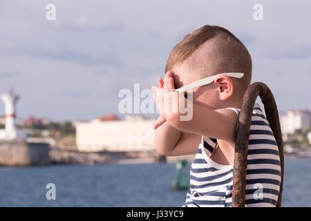 Little Boy in occhiali da sole si copre il viso dal sole Foto Stock