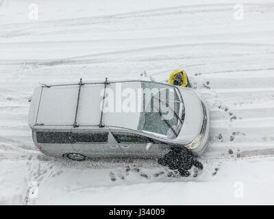 Una vista da sopra di due persone persone che cambiano il montaggio la rimozione di catene da neve su una neve strada Foto Stock