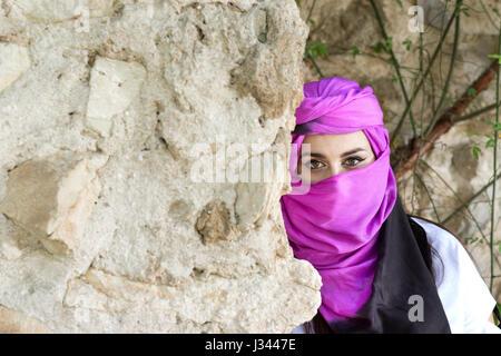 Ritratto di belle e mistero giovane donna indossa turbante guardando la fotocamera. Foto Stock
