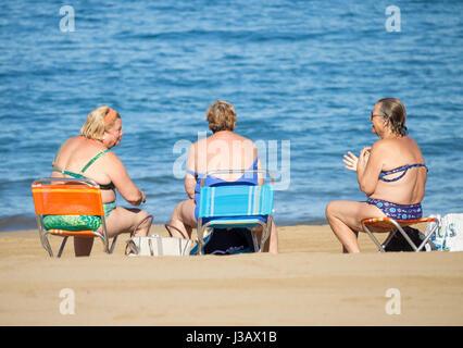 Tre anziani donna spagnola in chat sulla spiaggia dopo la nuotata mattutina. Foto Stock