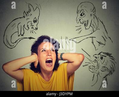 Male gli uomini malvagi rivolti a sottolineato la donna. Disperata paura giovane donna isolato su ufficio grigio Foto Stock