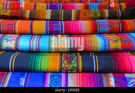 Un mucchio di tradizionali tessuti andina o prodotti tessili venduti sul mercato di artigianato di Otavalo, Ecuador. Foto Stock