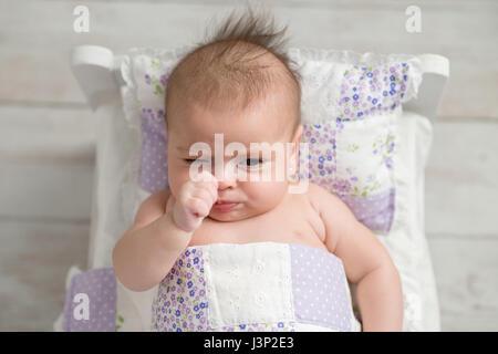 Un overhead shot di quattro mesi di età, il broncio, bambina. Ella è giacente in un piccolo letto matrimoniale con Foto Stock