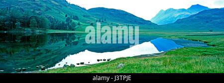 Ancora un silenzio mattina all'iconico Blea Tarn nel Lake District Cumbria con le colline e Langdale Pikes in background Foto Stock