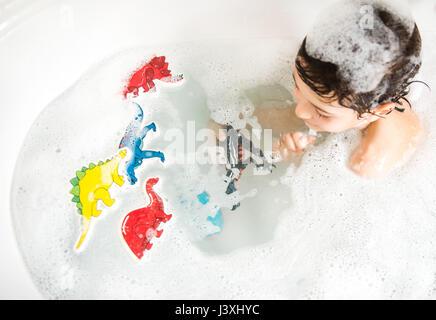 Ragazzo giocando con i giocattoli in bagno, vista in elevazione Foto Stock