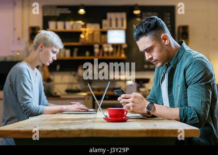 Uomo e donna che lavorano su computer portatili a tavola in cafe Foto Stock