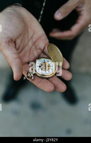 Uomo che indossa tuta, azienda orologio da tasca in mano, vista in elevazione, close-up Foto Stock
