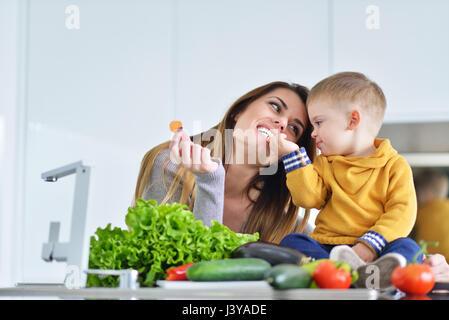La madre e il bambino a preparare il pranzo da verdure fresche Foto Stock