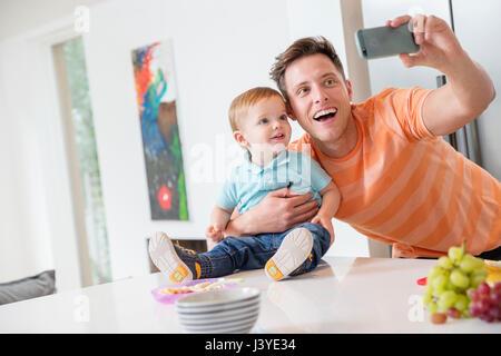 Padre e figlio toddler tenendo selfie in cucina a casa Foto Stock
