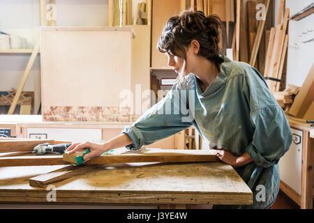 Giovane donna la levigatura del legno in un workshop Foto Stock
