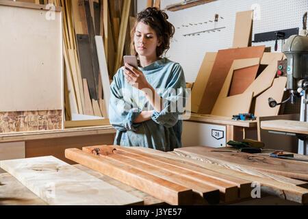 Giovane donna texting in un workshop di legno Foto Stock
