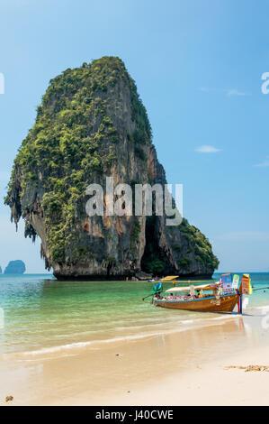 Vista panoramica della spiaggia e longtail boat contro la montagna erosa dal mare Foto Stock