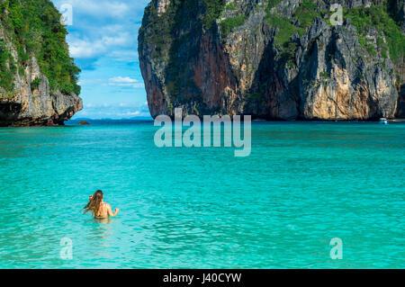 Vista panoramica della donna da parte di mare contro le formazioni rocciose Foto Stock