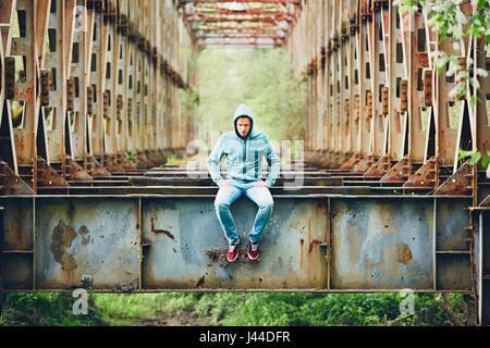 Triste uomo seduto sull'abbandonato ponte arrugginito. Concetto di tristezza e di solitudine e di più.