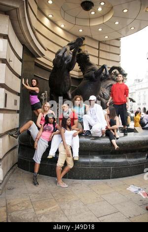 Gruppo misto di giovani danzatori che pongono a Leicester Square, London, Regno Unito Foto Stock