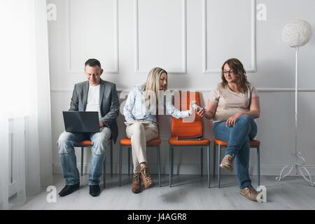 Un gruppo di giovani creativi seduti su sedie in sala d'attesa Foto Stock