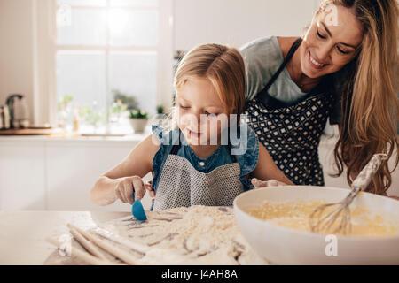 Colpo di bambina aggiungendo farina per la pastella in una terrina. Madre insegnare a sua figlia di cucinare nella Foto Stock
