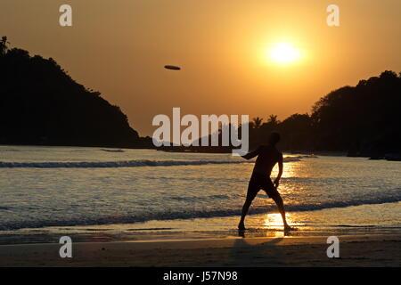 L'uomo la riproduzione di Frisbee sulla spiaggia di Palolem, India del Sud, Goa, Agonda, Arambol, Anjuna,Cola lato Foto Stock