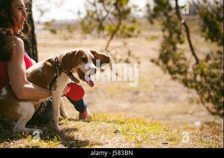 I giovani animali di razze di cani beagle passeggiate nel parco all'aperto. donna cammina con cautela cucciolo, gioca e tranitsiruetsya, si siede con PET in un abbraccio sotto agli alberi o Foto Stock