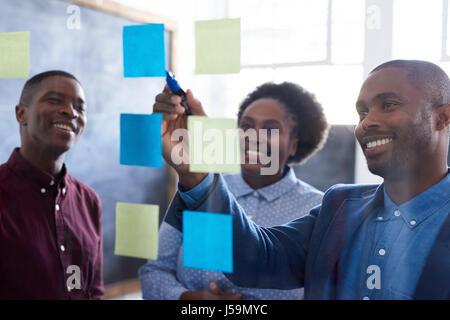 Positivo lavoro africana ai colleghi il brainstorming insieme in un ufficio Foto Stock