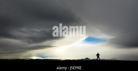 Silhouette di uomo guarda enorme tempesta e nuvole in Islanda Foto Stock