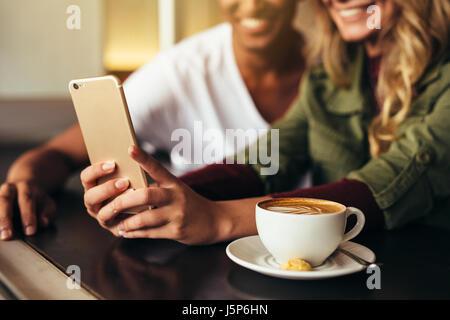 Chiusura del giovane uomo e donna seduta insieme al cafe e tenendo selfie con il telefono cellulare. Amici facendo selfie presso la caffetteria utilizzando smart phone. Foto Stock