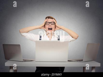 Sottolineato imprenditrice seduta al tavolo di fronte a più computer nel suo ufficio di esaurimento nervoso. Negativo Foto Stock