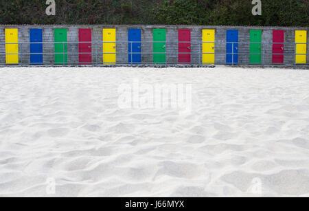 Una fila di cabine sulla spiaggia, con vivaci e colorati porte su una spiaggia di sabbia bianca con copia spazio Foto Stock