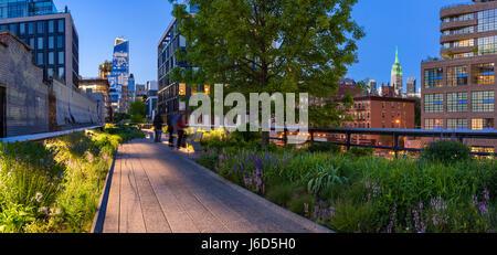 Highline vista panoramica al crepuscolo con le luci della città illuminata di grattacieli e grattacieli. Chelsea, Foto Stock