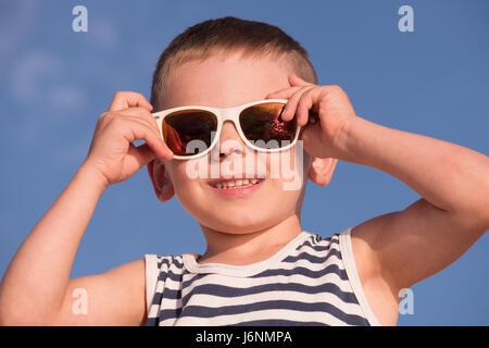 Sorridenti little boy indossando occhiali da sole con vista oceano tramonto riflesso e camicia a righe blu su sfondo Foto Stock
