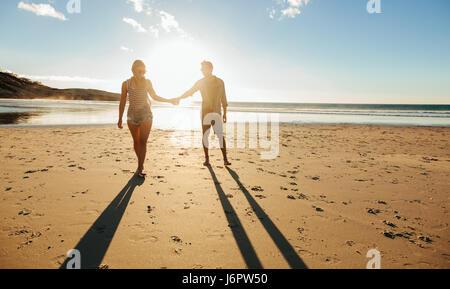 Colpo all'aperto di romantica coppia giovane camminando lungo la riva del mare tenendo le mani. Giovane uomo e donna Foto Stock