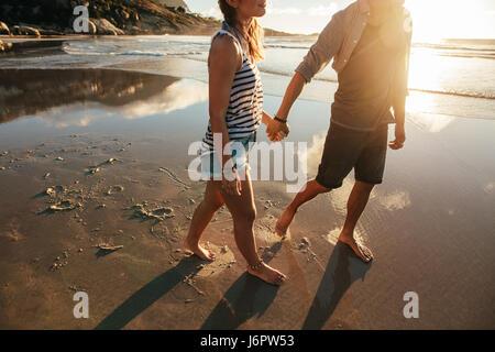 Colpo all'aperto di amorevole coppia giovane camminando sulla riva del mare tenendo le mani. Giovane uomo e donna Foto Stock