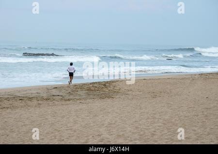 Lone runner maschio lungo la Playa Bruja spiaggia dietro le onde dell'Oceano Pacifico in un giorno nuvoloso al RIU Foto Stock