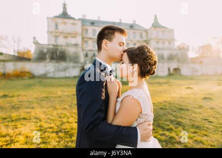 Il govern è baciare la bella sposa in fronte al background dell antico castello gotico durante il tramonto. Vista da vicino