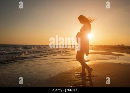 Silhouette di una donna in stato di gravidanza di camminare sulla spiaggia al tramonto Foto Stock