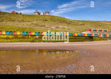 Spiaggia di capanne di rivestimento del lungomare e riflettendo in una piscina alla spiaggia del Nord, Whitby, North Foto Stock