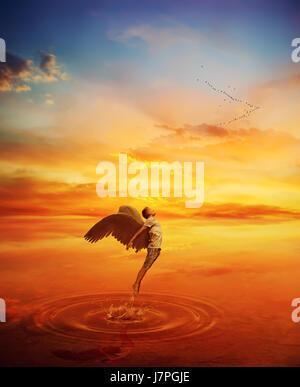 Immagine surrealista come angelo provare a saltare da un lago di acqua e volare lontano. Grande fuga spirituale Foto Stock