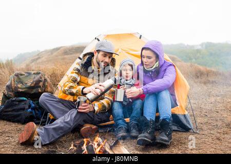 Famiglia con un bambino seduto vicino alla tenda e di bere il tè caldo da thermos durante il riposo in prossimità Foto Stock