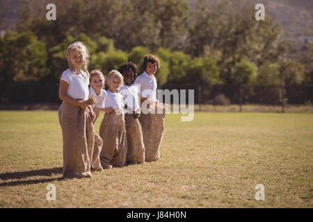 Ritratto di felice studentesse in piedi nel sacco durante la gara in una giornata di sole Foto Stock