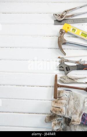 Vista aerea di attrezzi di lavoro su bianco tavolo in legno