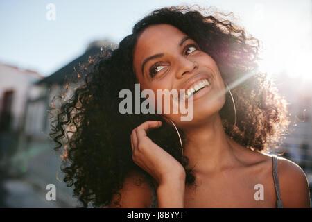 Close up ritratto di giovane donna africana con capelli ricci guardando lontano. Afro American femmina esterno permanente e sorridente.