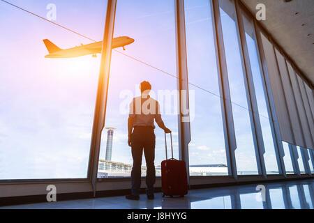 Imprenditore con la valigia in aeroporto internazionale di gate di partenza guardando Battenti aereo attraverso le finestre Foto Stock