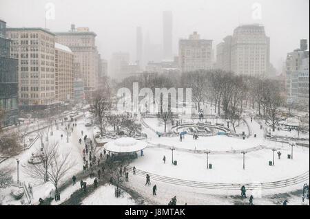 Nevoso inverno scena con sentieri a sinistra da pedoni nella neve in Union Square come una bufera di neve si impadronisce di New York City Foto Stock