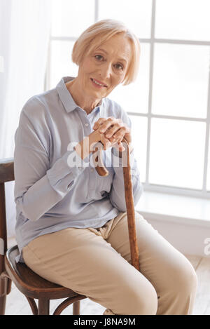 Sentevi. Felice anziani donna seduta sulla sedia piegando il capo mentre guardando dritto in telecamera Foto Stock