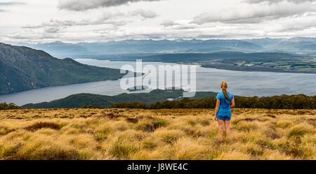 Escursionista femmina guardando il Lago Te Anau e Southfiord, Keplero via, Parco Nazionale di Fiordland, Southland, Foto Stock