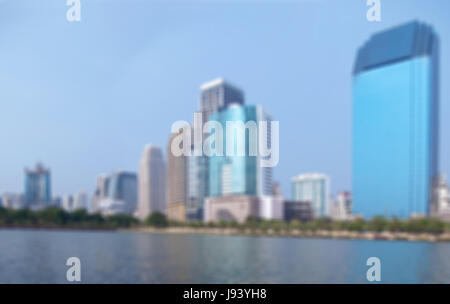 Abstract cityscape sfocate con il lago e alto edificio. Foto Stock