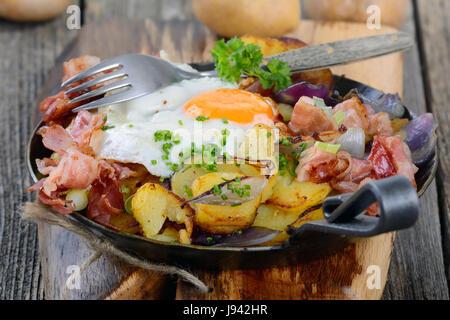 Agricoltore e la colazione con patate fritte, uova fritte e bacon e servita in una padella di ferro Foto Stock