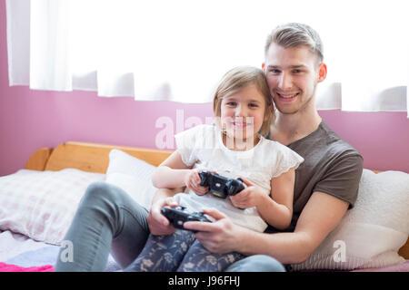 Fratello e sorella più piccola giocando a letto Foto Stock