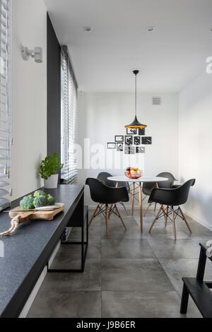 Cucina bianca con lungo bancone in granito, tavolo rotondo e ...