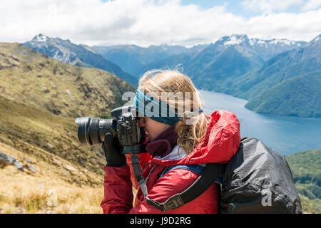 Giovane donna di scattare una foto, Keplero via, Parco Nazionale di Fiordland, Southland, Nuova Zelanda Foto Stock